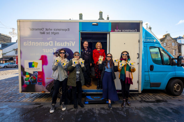 Dementia-Experience-Bus-Maggie-Ellis-and-Group-Outside-with-hands-up-A97A4725-low-res